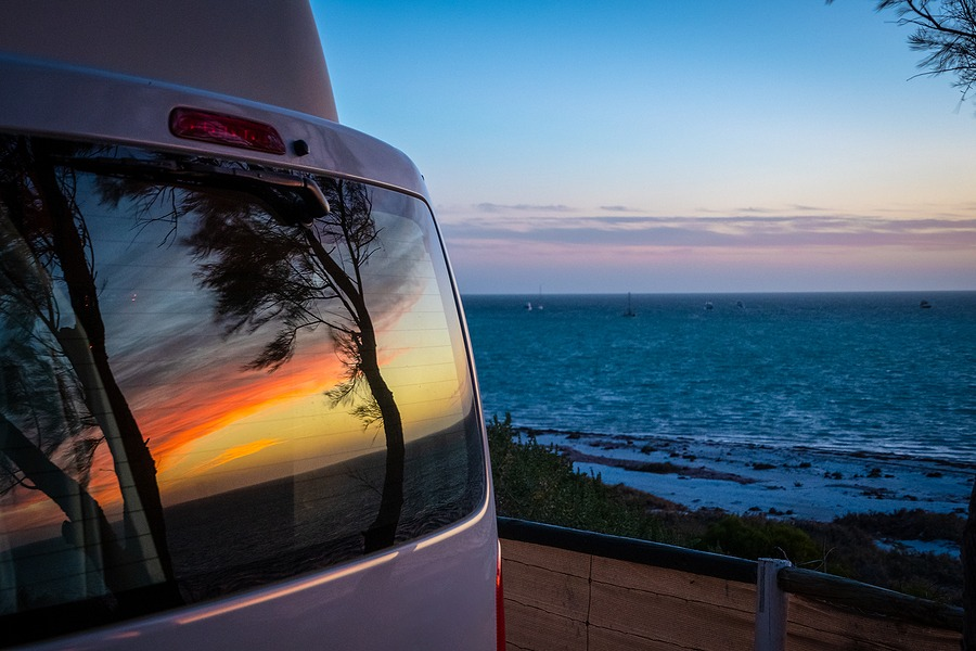 Reflection Of Tree Silhouettes On Campervan Window In Front Of I